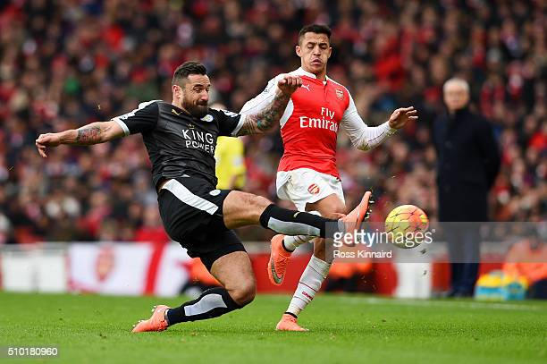 Marcin Wasilewski of Leicester City slides in to clear the ball from Alexis Sanchez of Arsenal during the Barclays Premier League match between...