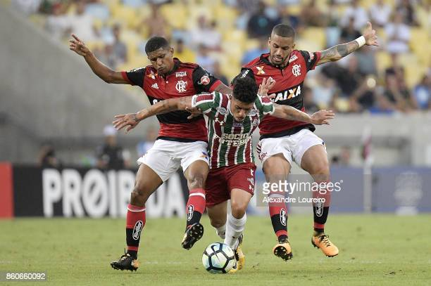 Marcio Araujo and Romulo of Flamengo battles for the ball with Douglas of Fluminense during the match between Flamengo and Fluminense as part of...