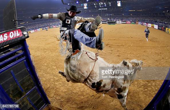Marco Antonio Eguchi of Brazil gets bucked off of Bottoms Up in the first round of the PBR Frontier Communications Iron Cowboy at ATT Stadium on...