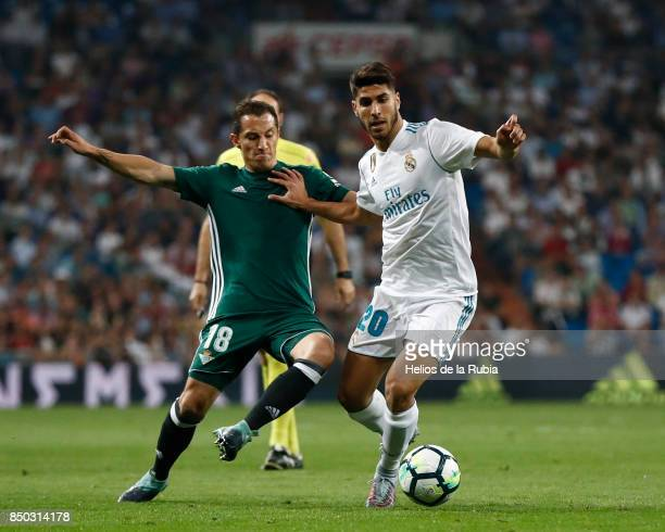 Marco Asensio of Real Madrid and Andres Guardado of Real Betis compete for the ball during the La Liga match between Real Madrid and Real Betis at...