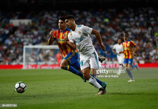 Marco Asensio of Real Madrid and Carlos Soler of Valencia cf compete for the ball during the La Liga match between Real Madrid and Valencia CF at...