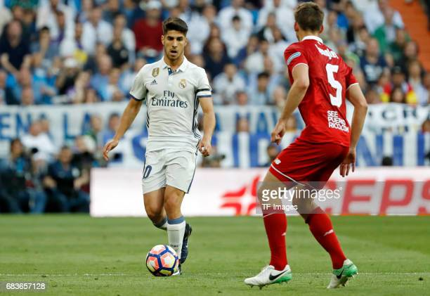 Marco Asensio of Real Madrid and Nenglet of Sevilla battle for the ball during the La Liga match between Real Madrid CF and Sevilla CF at Estadio...