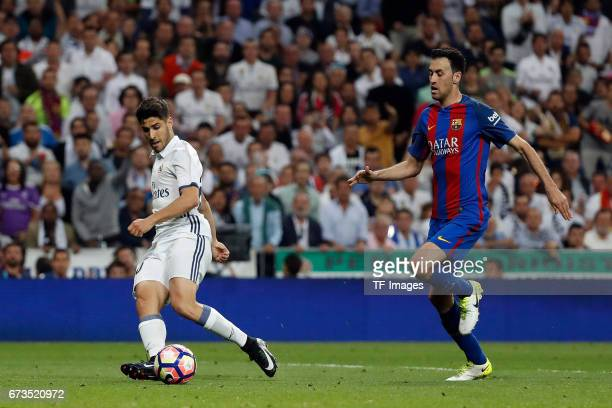 Marco Asensio of Real Madrid and Sergio Busquets of FC Barcelona battle for the ball during the La Liga match between Real Madrid CF and FC Barcelona...