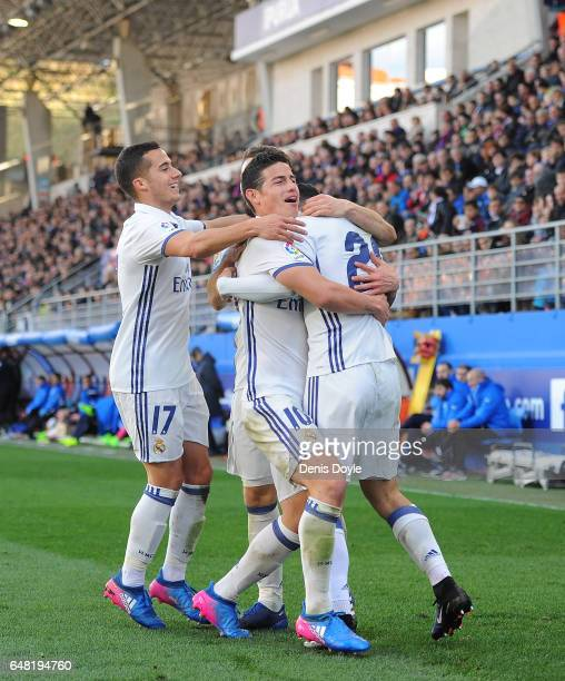 Marco Asensio of Real Madrid celebrates James Rodriguez and Lucas Vazquez after scoring Real's 4th goal during the La Liga match between SD Eibar and...