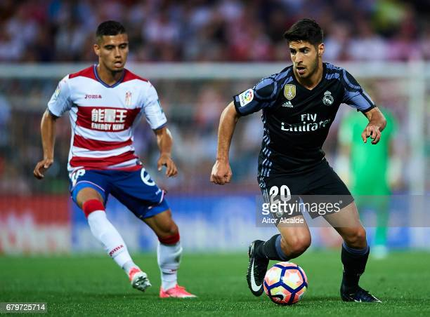 Marco Asensio of Real Madrid CF being followed by Andreas Pereira of Granada CF during the La Liga match between Granada CF v Real Madrid CF at...