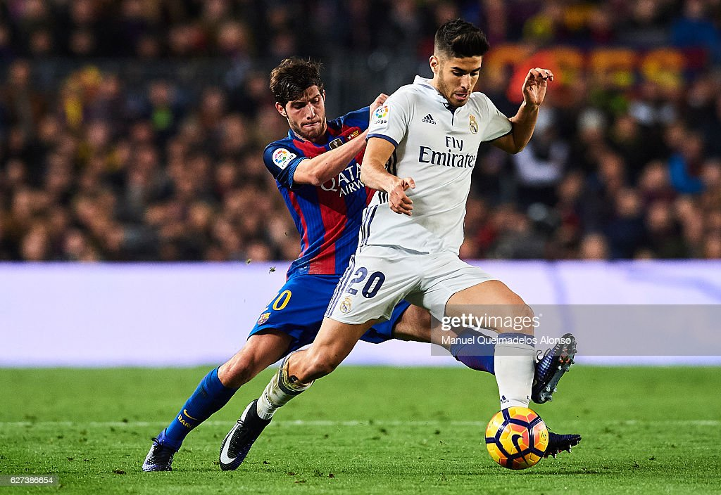 Marco Asensio of Real Madrid CF being followed by Sergio Roberto of FC Barcelona during La Liga match between FC Barcelona and Real Madrid CF at Camp...
