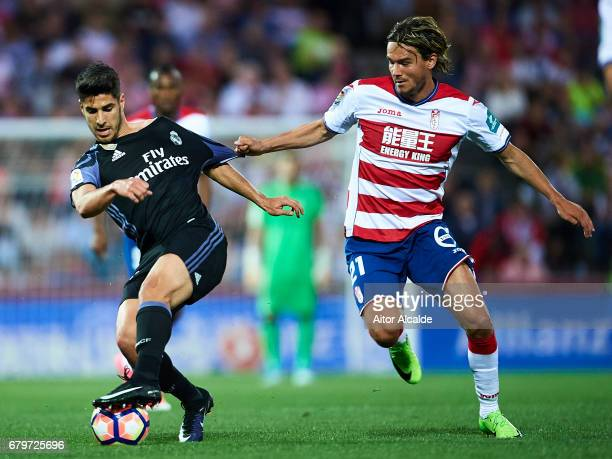 Marco Asensio of Real Madrid CF being fouled by Rene Krhin of Granada CF during the La Liga match between Granada CF v Real Madrid CF at Estadio...
