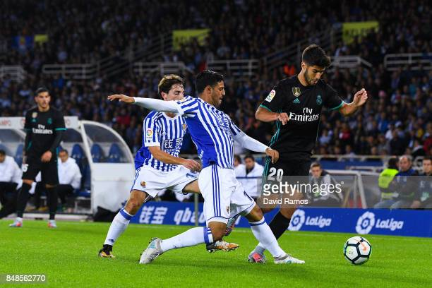 Marco Asensio of Real Madrid CF competes for the ball with Alvaro Odriozola and Carlos Vela of Real Sociedad de Futbol during the La Liga match...