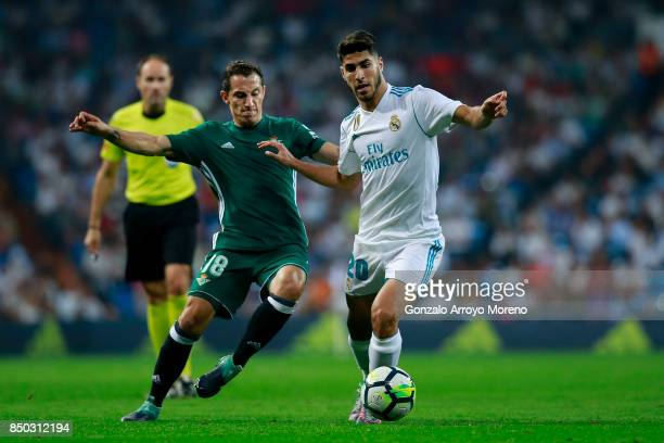 Marco Asensio of Real Madrid CF competes for the ball with Andres Guardado of Real Betis Balompie during the La Liga match between Real Madrid CF and...