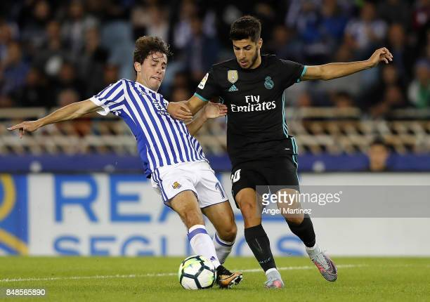 Marco Asensio of Real Madrid competes for the ball with Alvaro Odriozola of Real Sociedad during the La Liga match between Real Sociedad and Real...