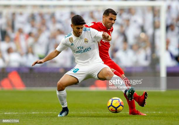 Marco Asensio of Real Madrid competes for the ball with Clement Lenglet of Sevilla during the La Liga match between Real Madrid and Sevilla at...