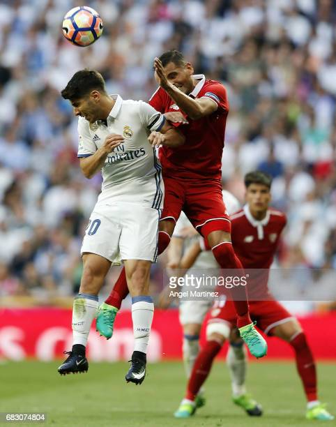 Marco Asensio of Real Madrid competes for the ball with Gabriel Mercado of Sevilla FC during the La Liga match between Real Madrid and Sevilla FC at...