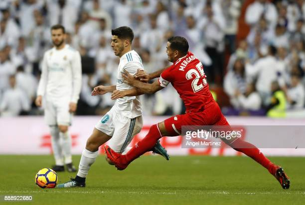 Marco Asensio of Real Madrid competes for the ball with Gabriel Mercado of Sevilla during the La Liga match between Real Madrid and Sevilla at...