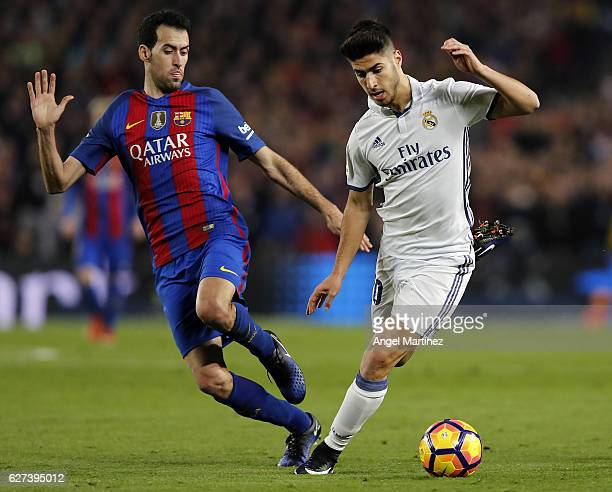 Marco Asensio of Real Madrid competes for the ball with Sergio Busquets of FC Barcelona during the La Liga match between FC Barcelona and Real Madrid...