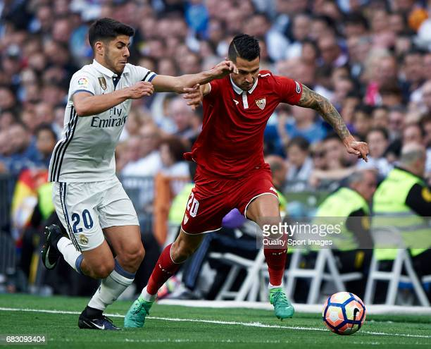 Marco Asensio of Real Madrid competes for the ball with Vitolo of Sevilla during the La Liga match between Real Madrid CF and Sevilla CF at Estadio...