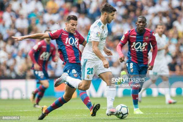 Marco Asensio of Real Madrid fights for the ball with Roberto Suarez Pier Rober of Levante UD during the La Liga match between Real Madrid and...