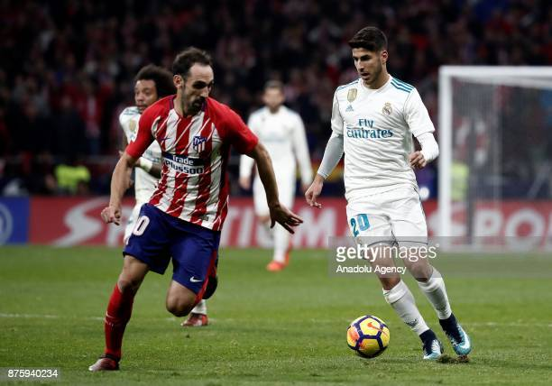 Marco Asensio of Real Madrid in action against Juanfran of Atletico Madrid during the Spanish La Liga match between Atletico Madrid and Real Madrid...