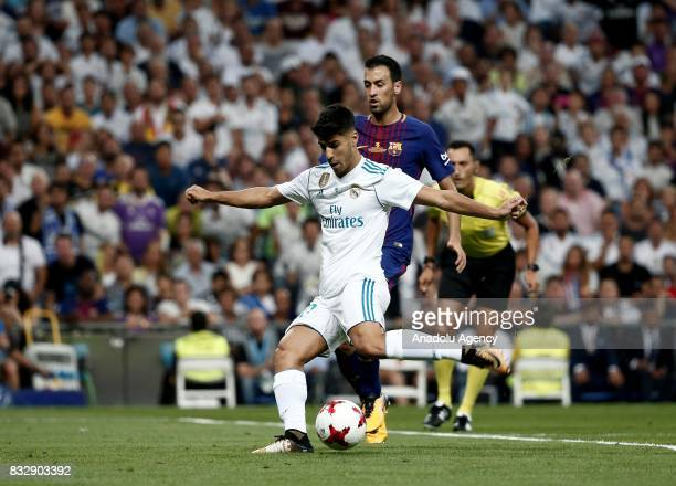 Marco Asensio of Real Madrid in action against Sergio Busquets of Barcelona during the Spanish Super Cup return match between Real Madrid and...