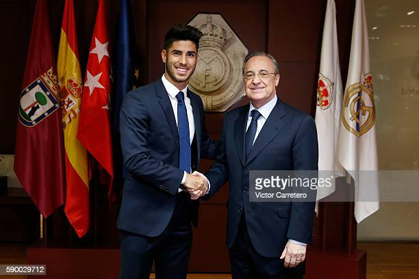 Marco Asensio of Real Madrid shakes hands with Real Madrid president Florentino Perez during his official presentation at Estadio Santiago Bernabeu...