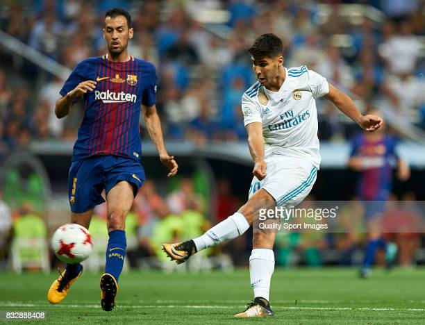 Marco Asensio of Real Madrid shoots on goal against Sergio Busquets of Barcelona during the Supercopa de Espana Supercopa Final 2nd Leg match between...