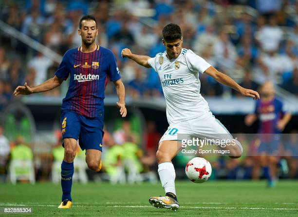 Marco Asensio of Real Madrid shoots to goal against Sergio Busquets of Barcelona during the Supercopa de Espana Supercopa Final 2nd Leg match between...