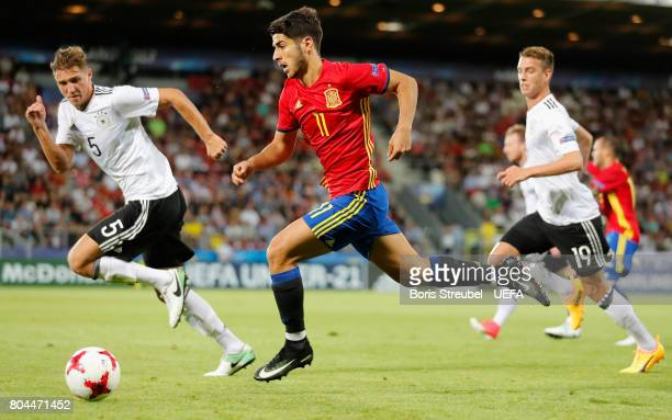 Marco Asensio of Spain attempts to get past Niklas Stark of Germany during the UEFA European Under21 Championship Final between Germany and Spain at...