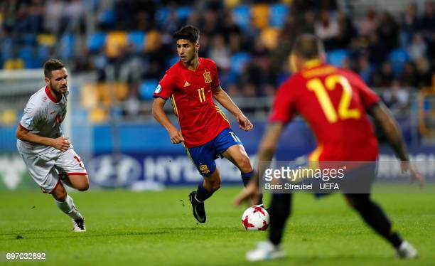 Marco Asensio of Spain is challenged by David Babunski of FYR Macedonia during the UEFA European Under21 Championship match between Spain and...