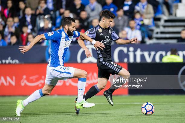 Marco Asensio Willemsen of Real Madrid battles for the ball with Lluis Sastre Reus of Deportivo Leganes during their La Liga match between Deportivo...