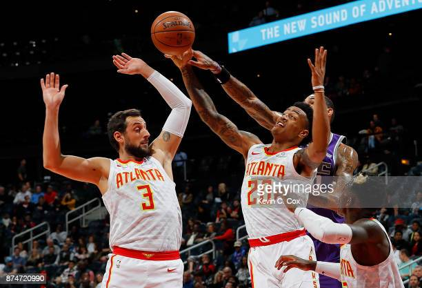 Marco Belinelli and John Collins of the Atlanta Hawks battle for a rebound against Willie CauleyStein of the Sacramento Kings at Philips Arena on...