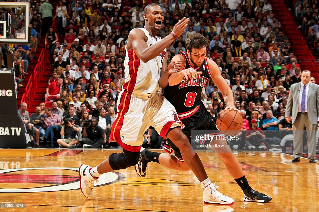Marco Belinelli #8 of the Chicago Bulls drives against Chris Bosh #1 of the Miami Heat on January 4, 2013 at American Airlines Arena in Miami, Florida.