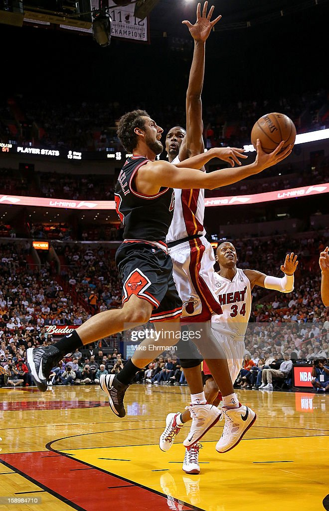 Marco Belinelli #8 of the Chicago Bulls drives past Chris Bosh #1 of the Miami Heat during a game at AmericanAirlines Arena on January 4, 2013 in Miami, Florida.