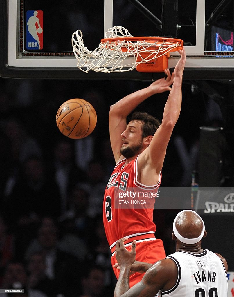 Marco Belinelli of the Chicago Bulls dunks over Reggie Evans of the Brooklyn Nets during Game 7 of the Eastern Conference quarterfinals at the Barclays Center May 4, 2013 in the Brooklyn borough of New York. The Bulls won, 99-93 to advance to the next round of playoffs against the Miami Heat. AFP PHOTO/Stan HONDA