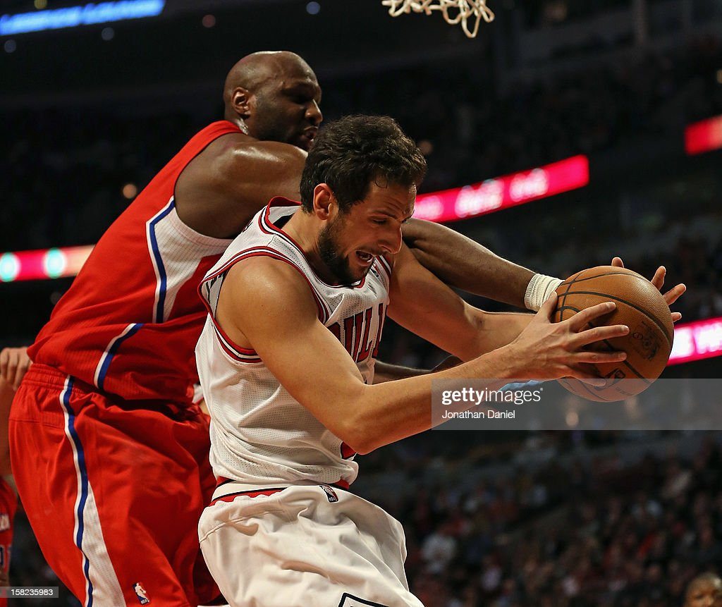Marco Belinelli #8 of the Chicago Bulls grabs a rebound under pressure from Lamar Odom #7 of the Los Angeles Clippers at the United Center on December 11, 2012 in Chicago, Illinois.