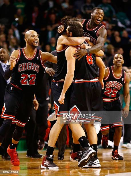 Marco Belinelli of the Chicago Bulls is embraced by teammates Joakim Noah and Nate Robinson of the Chicago Bulls after scoring the gamewinning shot...