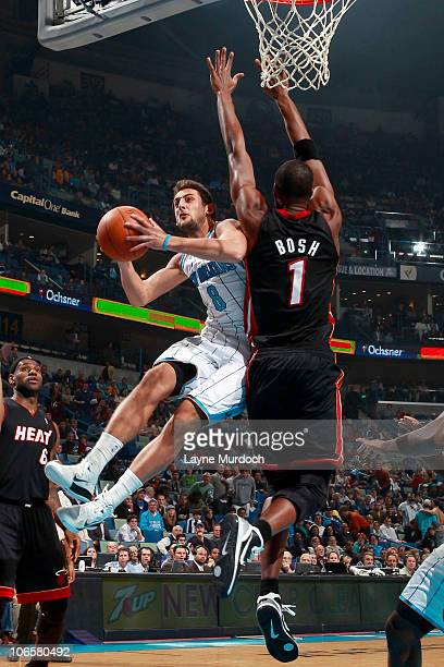 Marco Belinelli of the New Orleans Hornets attempts a shot while being defended by Chris Bosh of the Miami Heat on November 5 2010 at the New Orleans...