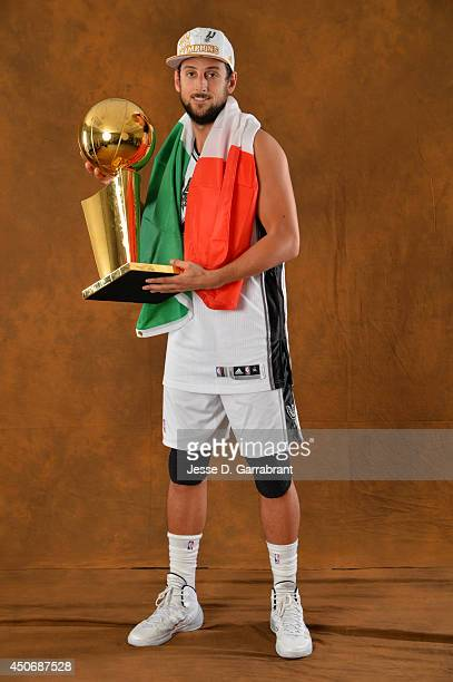 Marco Belinelli of the San Antonio Spurs poses for a portrait with the Larry O'Brien Trophy after defeating the Miami Heat in Game Five of the 2014...
