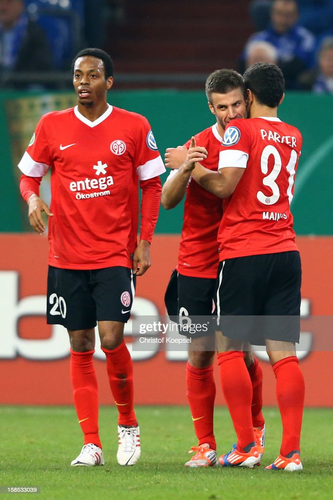 Marco Calliguri of Mainz (C) celebrates the first goal with Junior Diaz (L) and Shawn Parker of Mainz (R) during the DFB cup round of sixteen match between FC Schalke 04 and FSV Mainz 05 at Veltins-Arena on December 18, 2012 in Gelsenkirchen, Germany.