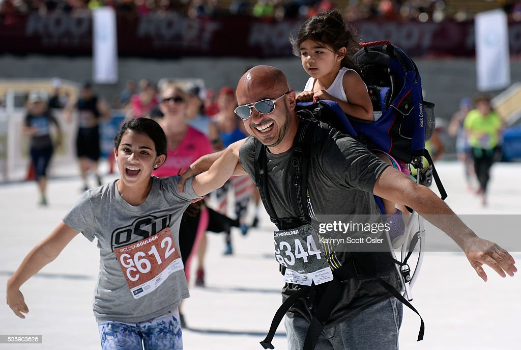 Marco Campos of Denver along with his two daughters, Carly, 12, left, and Nya, 3, help eachother across the finish line. The 38th BolderBOULDER takes place along Boulder's streets with the finish line of the 10k race at Folsom Field on the University of Colorado campus on Monday, May 30, 2016.