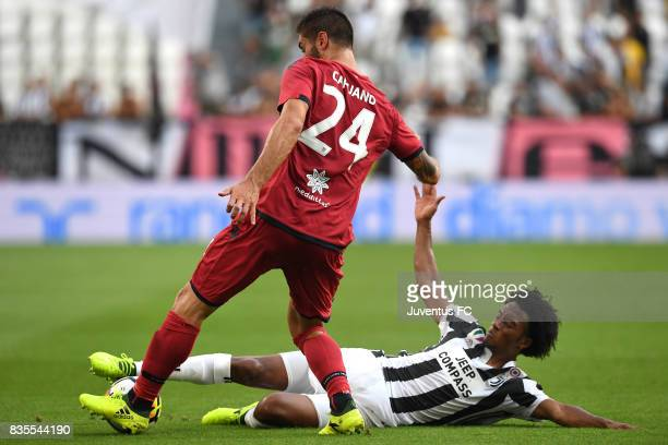 Marco Capuano of Cagliari is tackled by Juan Cuadrado of Juventus during the Serie A match between Juventus and Cagliari Calcio at Allianz Stadium on...