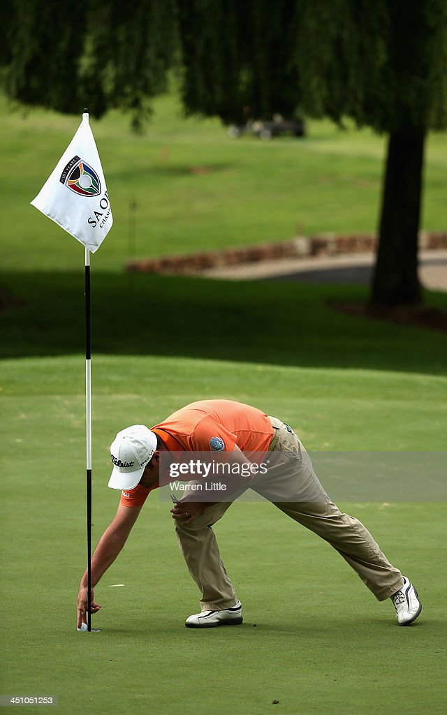 Marco Crespi of Italy retrieves his ball from the hole after making an eagle on the seventh hole during the first round of the South African Open Championship at Glendower Golf Club on November 21, 2013 in Johannesburg, South Africa.