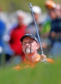 Marco Dawson watches his shot to the 18th green from a fairway sand trap during the third round of the 2014 Senior PGA Championship presented by...