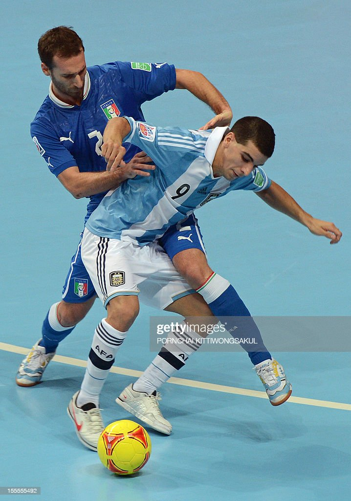Marco Ercolessi of Italy (L) battles for the ball with Cristian Borruto of Argentina (R) during their first round football match of the FIFA Futsal World Cup 2012 in Bangkok on November 5, 2012. AFP PHOTO / PORNCHAI KITTIWONGSAKUL
