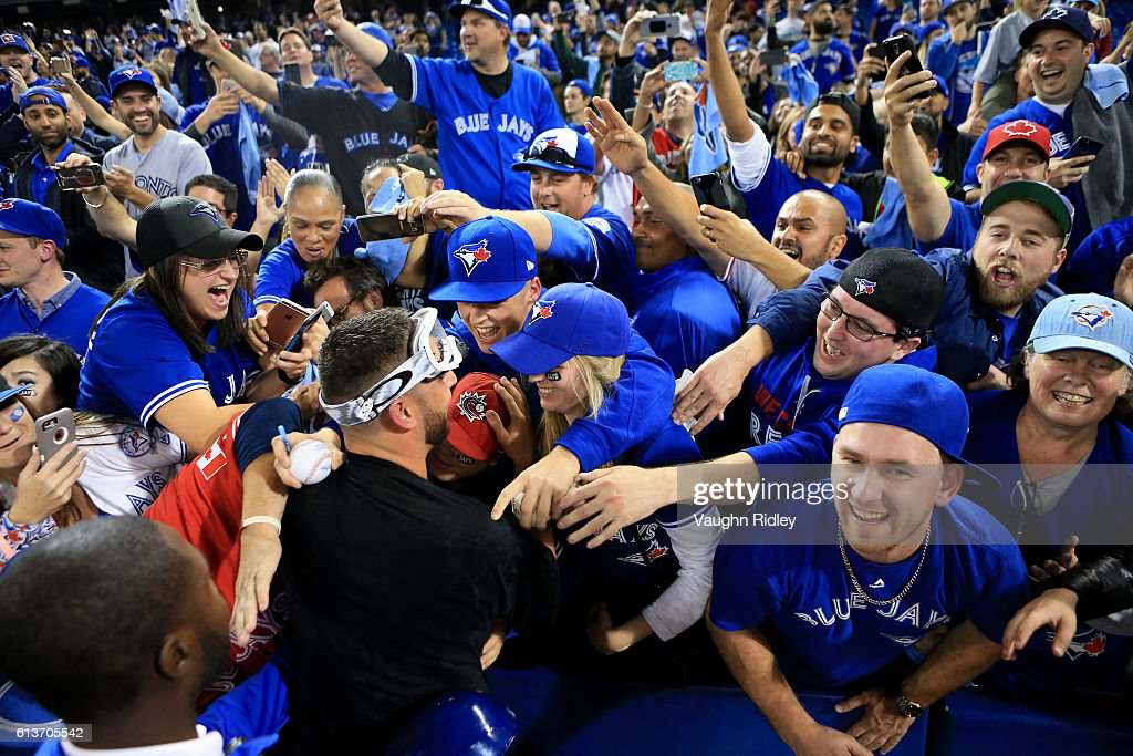 Marco Estrada #25 of the Toronto Blue Jays is swarmed by fans after the Toronto Blue Jays defeated the Toronto Blue Jays 7-6 for game three of the American League Division Series at Rogers Centre on October 9, 2016 in Toronto, Canada.