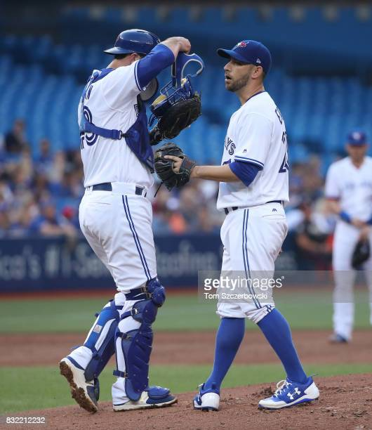 Marco Estrada of the Toronto Blue Jays is visited on the mound by Mike Ohlman in the second inning during MLB game action against the Tampa Bay Rays...