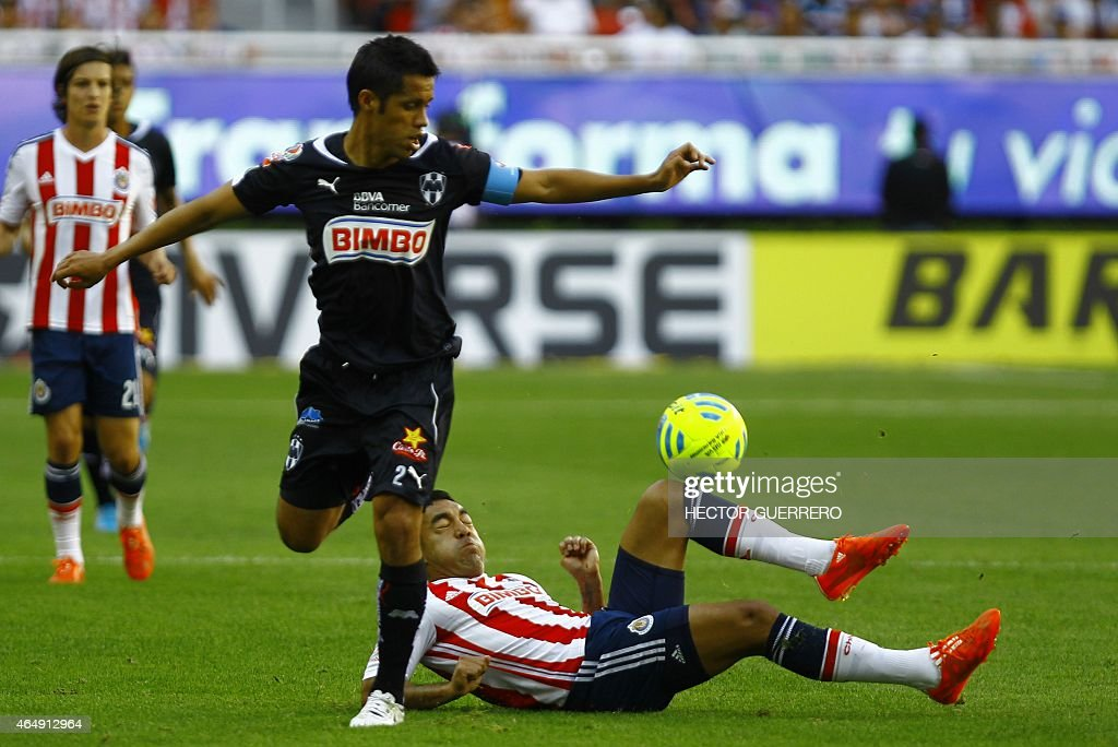 Marco Fabian of Chivas vies for the ball with Severo Meza of Monterrey during their Mexican Clausura 2015 tournament football match at Omnilife...