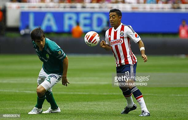 Marco Fabian of Chivas vies of the ball with Ignacio Gonzalez of Leon during their Mexican Clausura 2015 tournament football match at Omnilife...