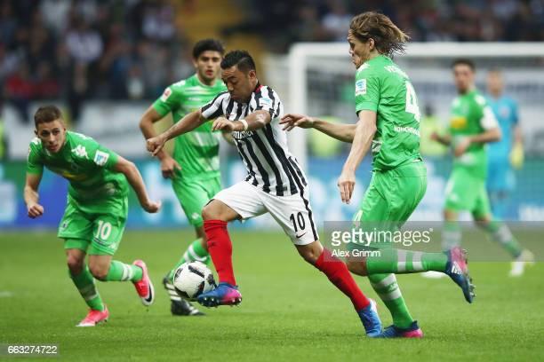Marco Fabian of Frankfurt is challenged by Jannik Vestergaard and Thorgan Hazard of Moenchengladbach during the Bundesliga match between Eintracht...
