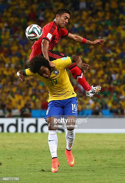 Marco Fabian of Mexico challenges Willian of Brazil during the 2014 FIFA World Cup Brazil Group A match between Brazil and Mexico at Castelao on June...