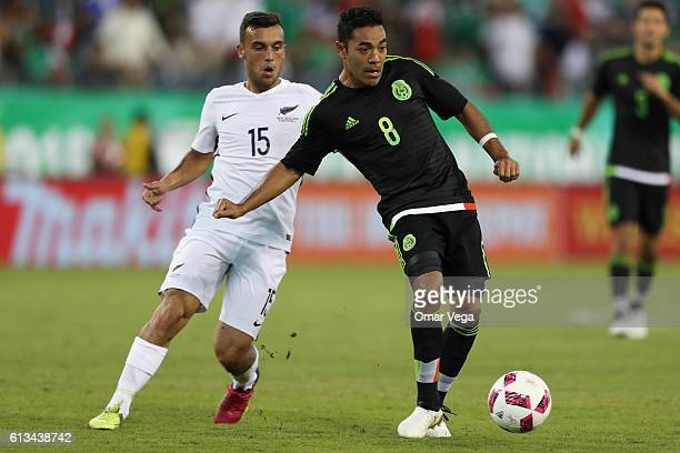 Marco Fabian of Mexico drives the ball while followed by Clayton Lewis of New Zealand during the International Friendly Match between Mexico and New...
