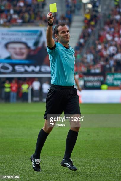 Marco Fritzshakes hands withow a yellow card during the Bundesliga match between FC Augsburg and Borussia Dortmund at WWKArena on September 30 2017...